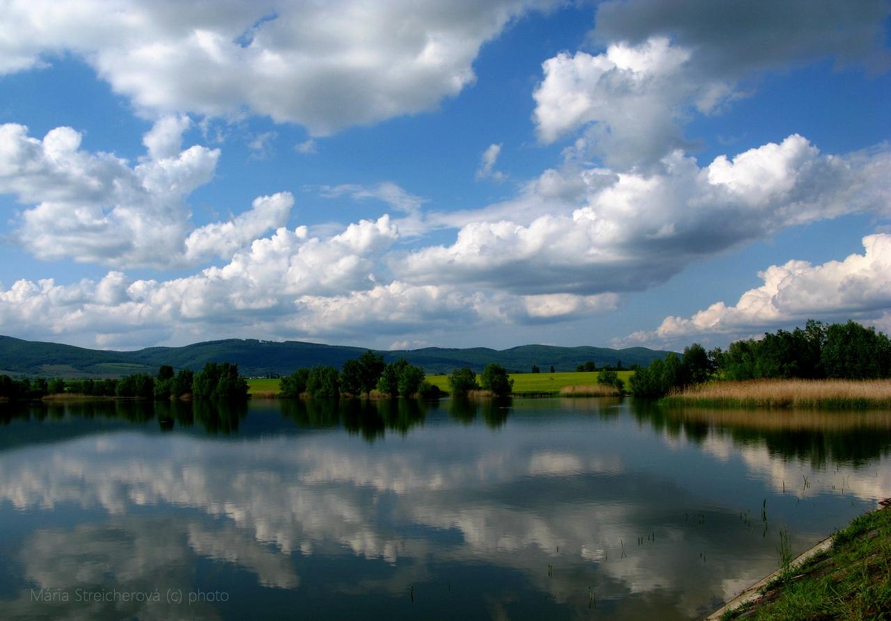 Letná krajina, modrá obloha s bielymi oblakmi a ich odraz v tichej hladine vodného zrkadla