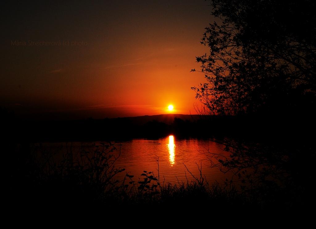 Oranžovočervený západ slnka za siluetou čiernych pahorkov a jeho odraz na jazernej hladine. V popredí siluety pobrežných rastlín, kríkov a stromov.