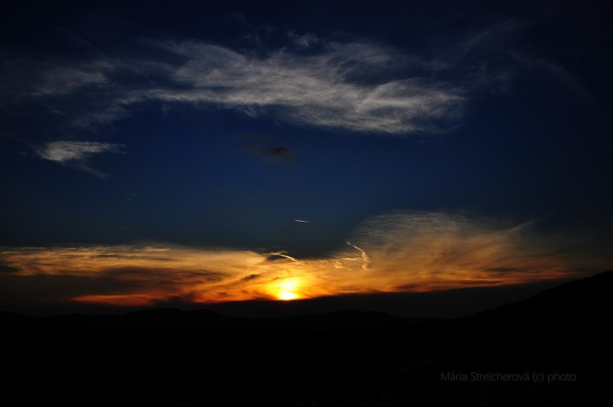"""Oranžovožltý západ slnka za čierny horizont pahorkov. Modrá tmavnúca obloha s riedkymi bielymi oblakmi. Nad slnkom malý čierny bod nadzvukového lietadla s krátkym """"chvostom"""" pary."""