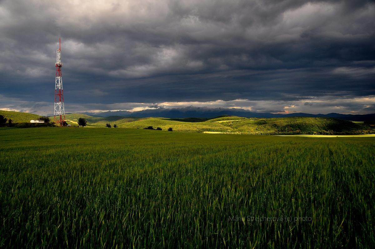 Zelené obilné pole, zamračená obloha a lúče zapadajúceho slnka vykresľujúce v teréne vzdialené polia a lúky. Červeno biela kovová konštrukcia vysielača.