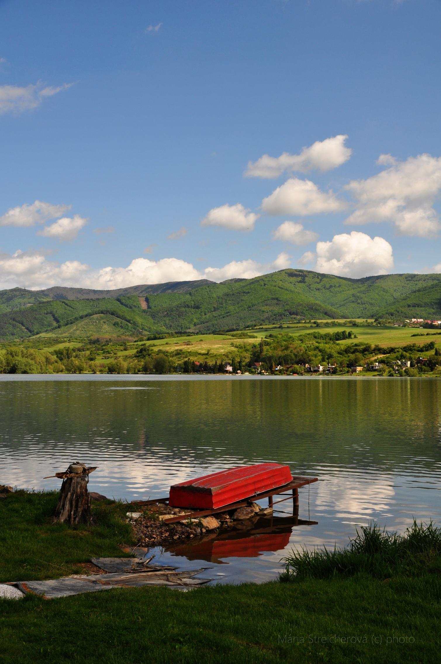 Vodná nádrž, priehrada, v májovom plnom slnku, v pozadí zeleé kopce a lúky, s modrým nebom a bielymi oblakmi. V popredí červený rybársky čln na móle, pri brehu, otočený hore dnom. Odrazy oblohy a krajiny vo vodnom zrkadle.