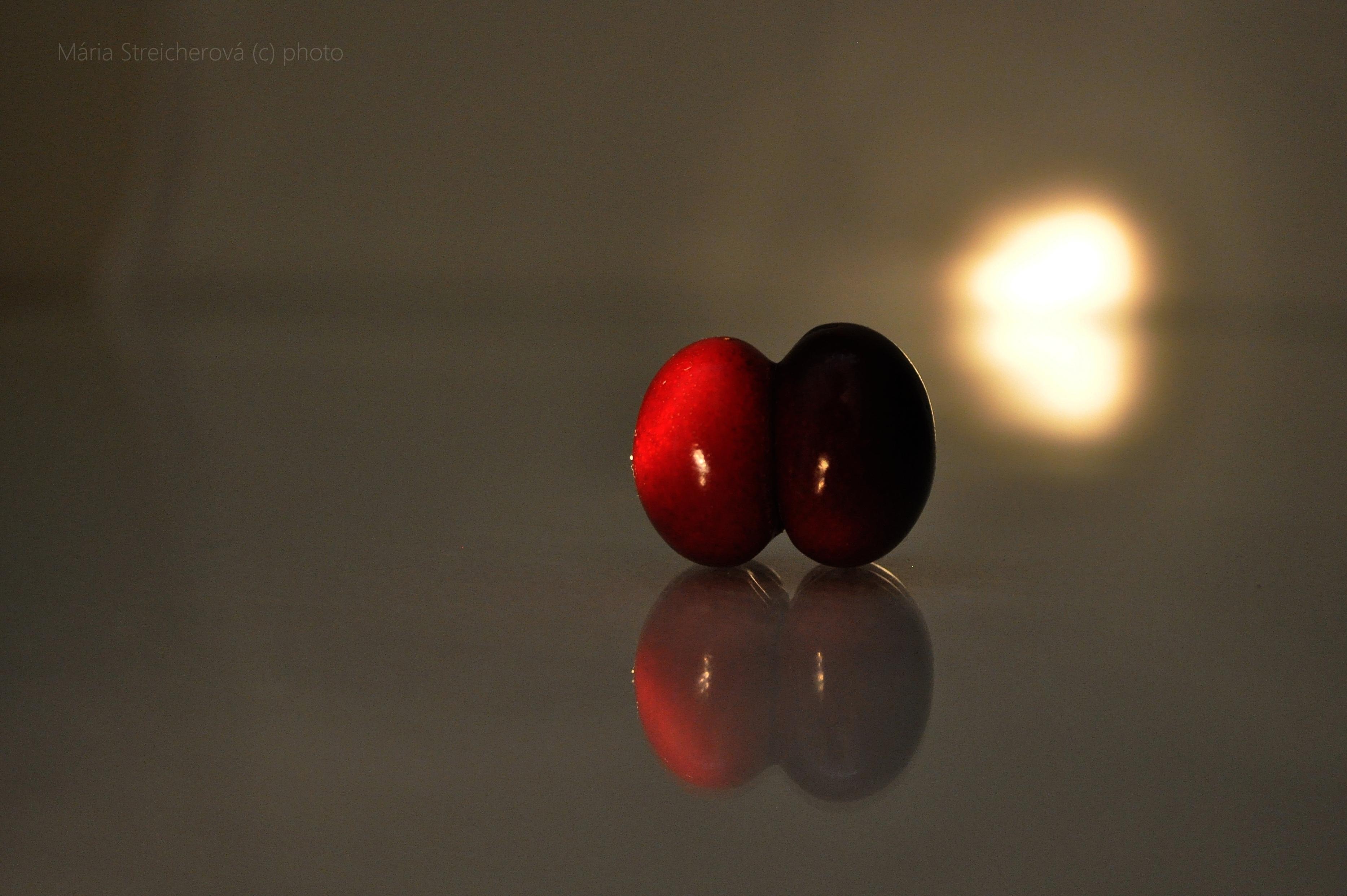 Zátišie s karmínovo červenými čerešňami zrastenými bruškom. Zrkadlový odraz čerešňových dvojičiek na skle.