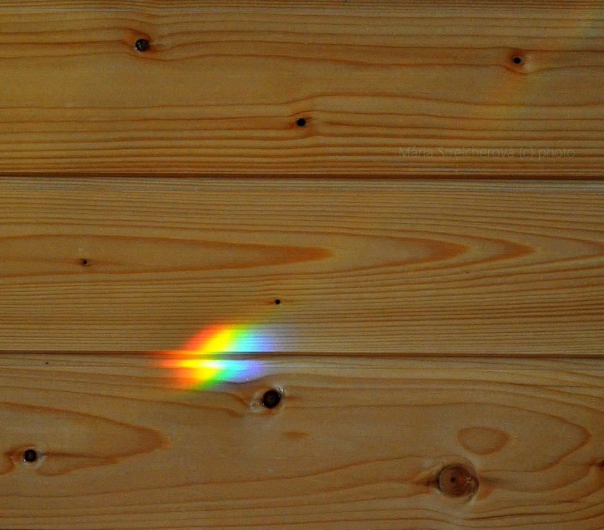 Fliačik farebného dúhového spektra na stene zo svetlého dreva
