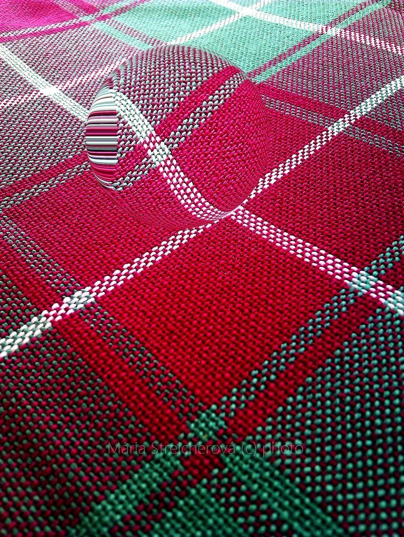 Textúra tkaného károvaného obrusa v červeno, zeleno bielej farbe s grafickou vsadkou šošovkového zväčšenia.