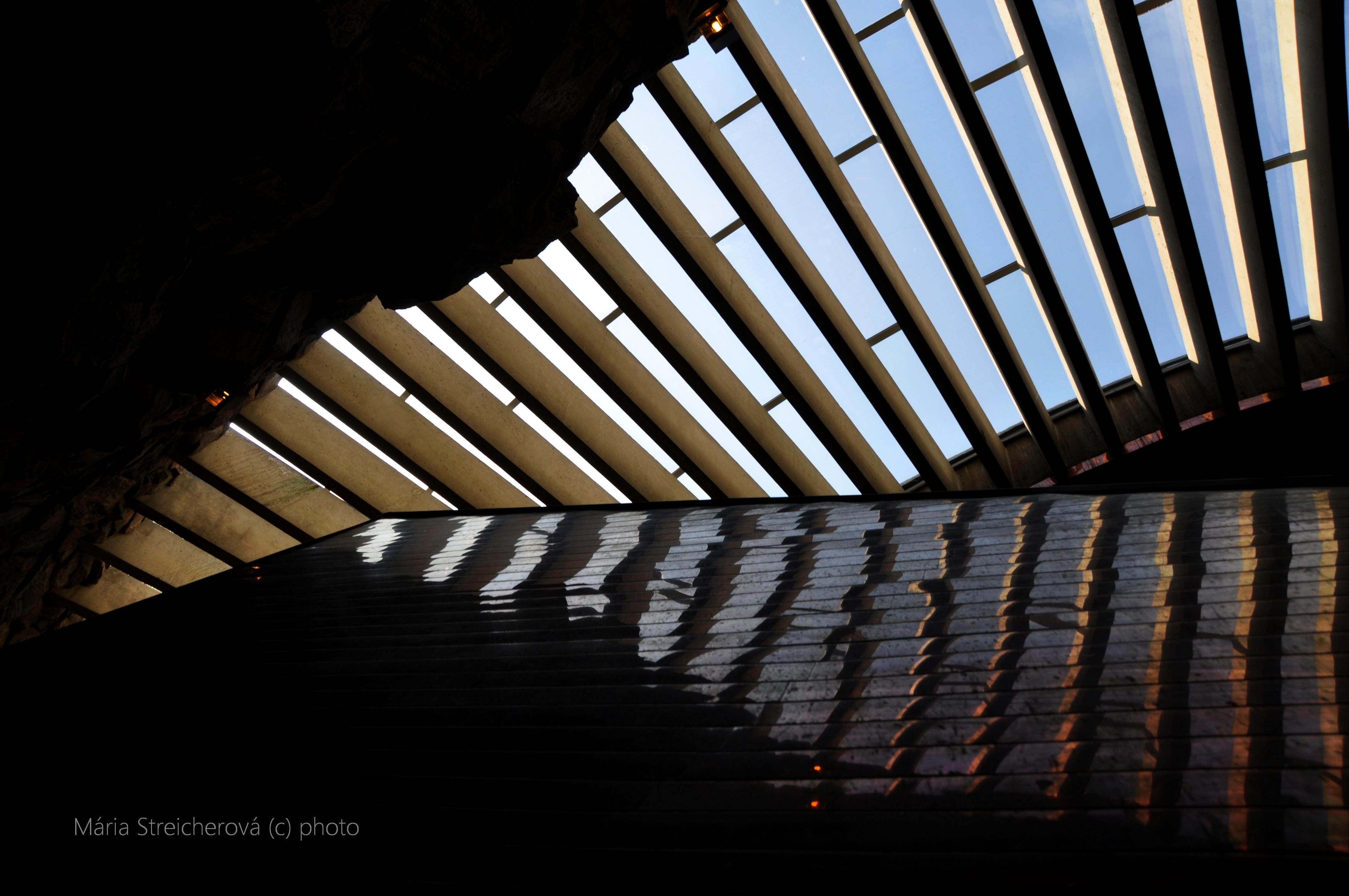 Stropné okná kostola Temppeliaukio v Kelsinkách a ich odraz v medenom obložení chórusu.