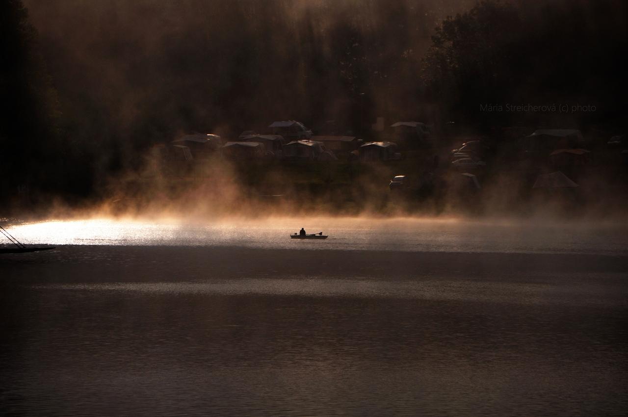 Ranné hmly nad vodnou hladinou a kempom na brehu priehrady, v lúčoch vychádzajúceho slnka. V prúde svetla silueta loďky s rybárom.