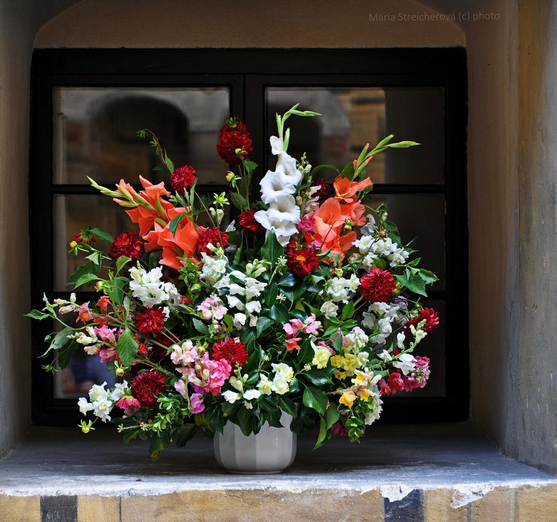 Veľká kytica pestrých kvetov naaranžovaná klasickým spôsobom, v bielej váze, umiestnená v nike zámockého okna, odvonku.