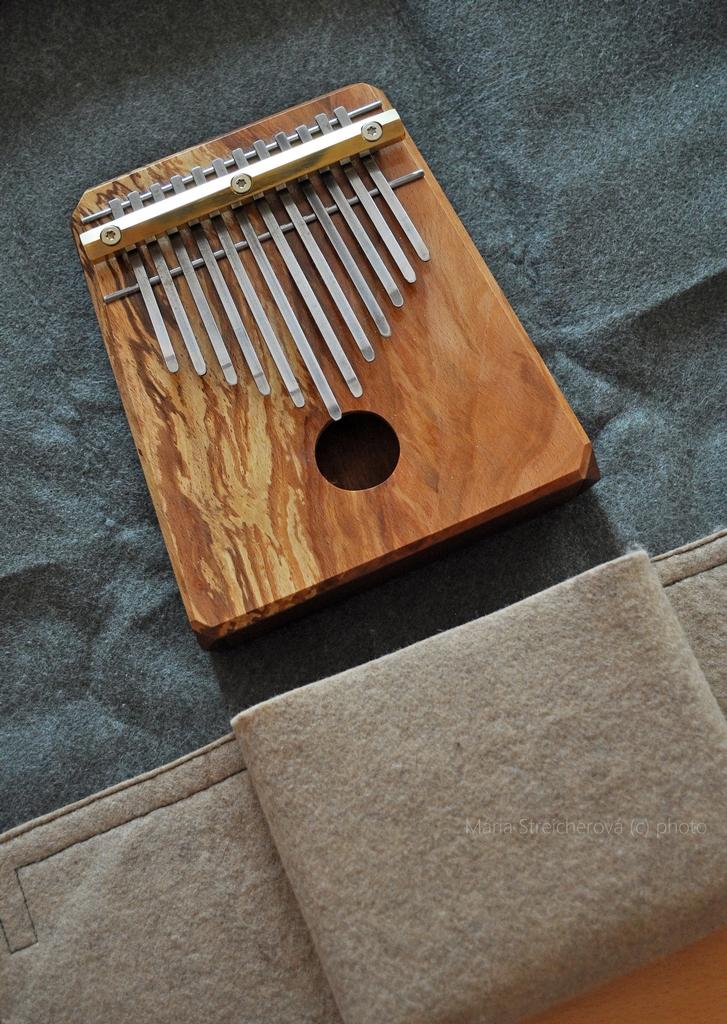 Kalimba z mahagónového dreva, s dvanástimi kovovými lamelami a ozvučnicou, položená na svojom sivom súkennom obale.