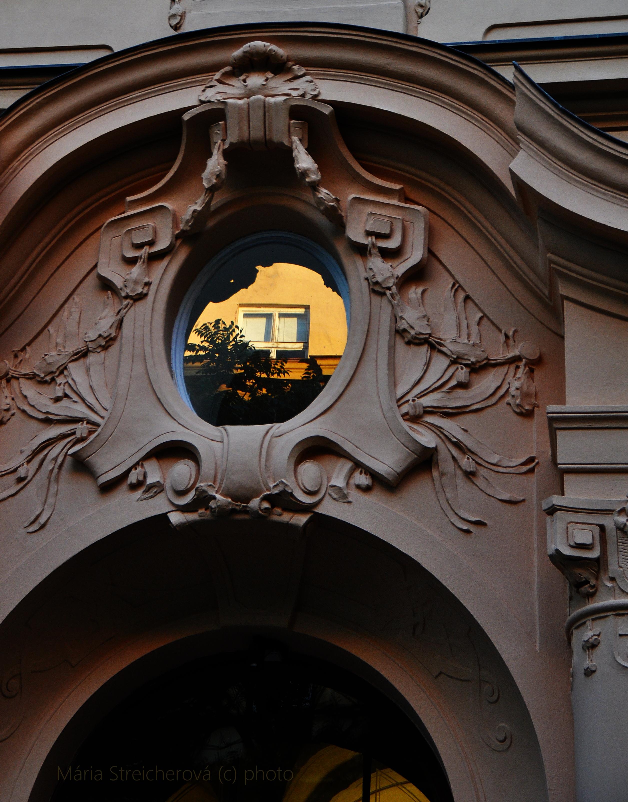 Odraz západom slnka osvetleného okna v oválnom okne nad portálom historickej budovy. Sivá štuková výzdoba okolo oválneho okna.