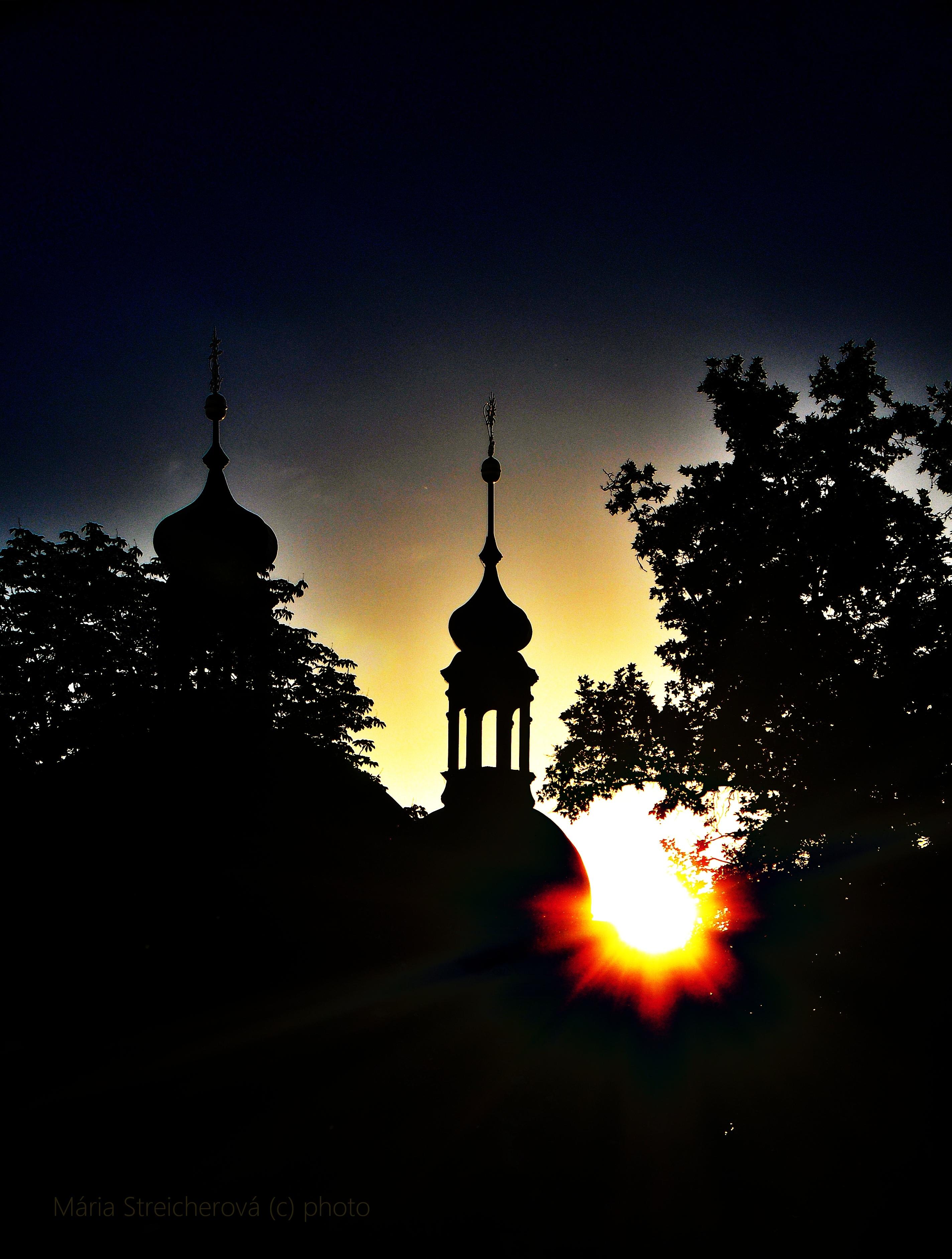 Silueta kopulovitých vežičiek kostola a stromov v protisvetle zapadajúceho slnka.