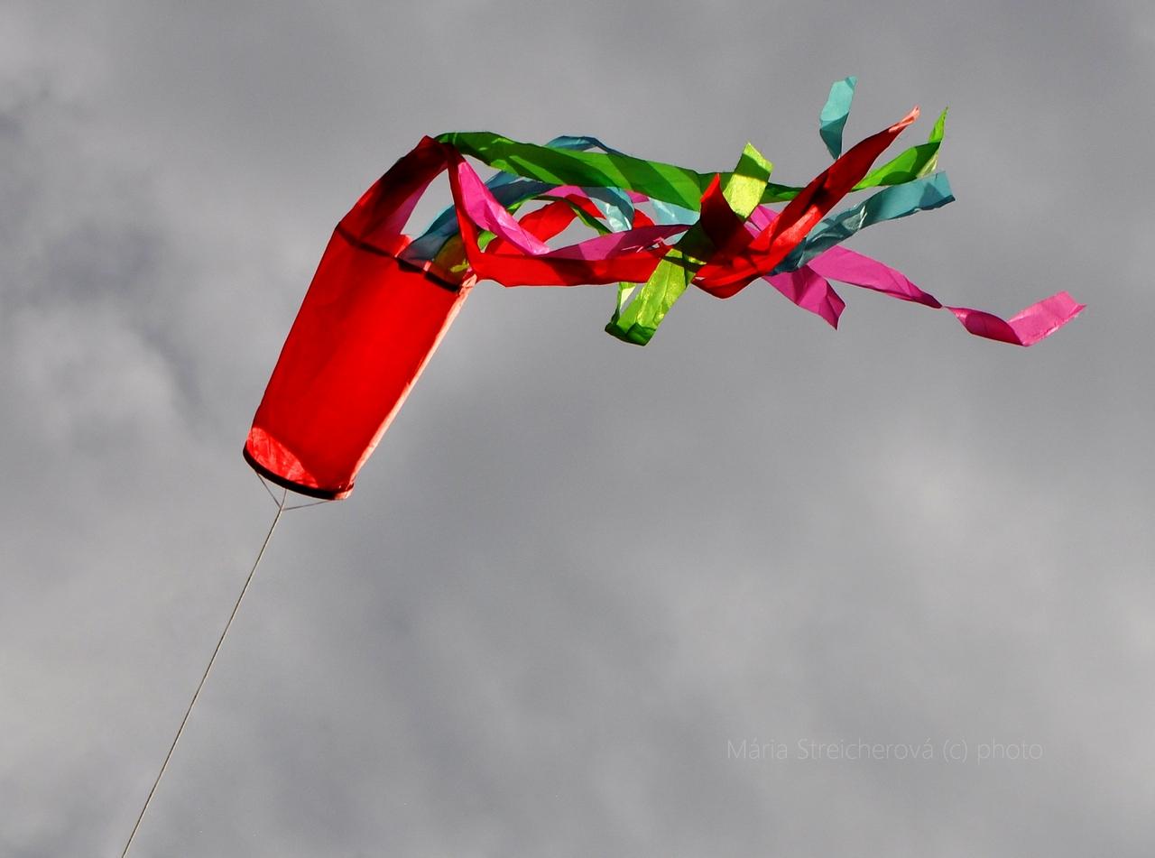 Červený veterný rukáv s rôznofarebnými stuhami nadutý stúpajúcim vetrom.