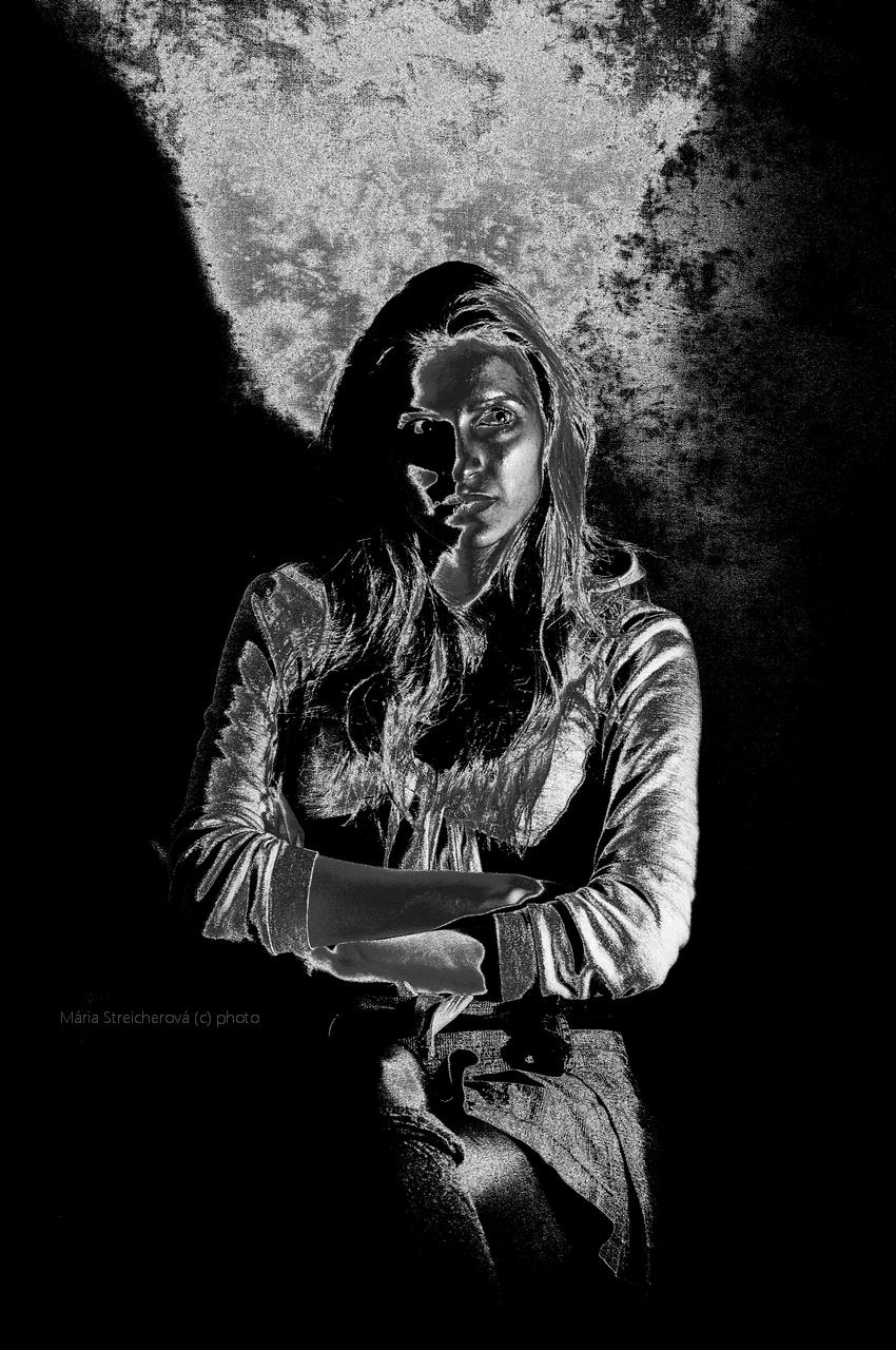 Záber hornej časti postavy sediacej mladej ženy v grafickej čierno bielej úprave.