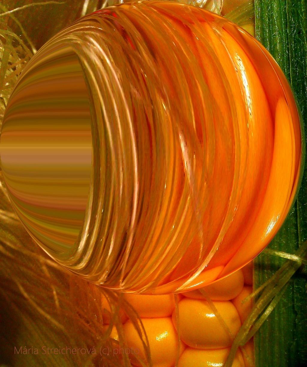 Detailný záber sčasti ošúpaného žltého kukuričného klasu v grafickej úprave.