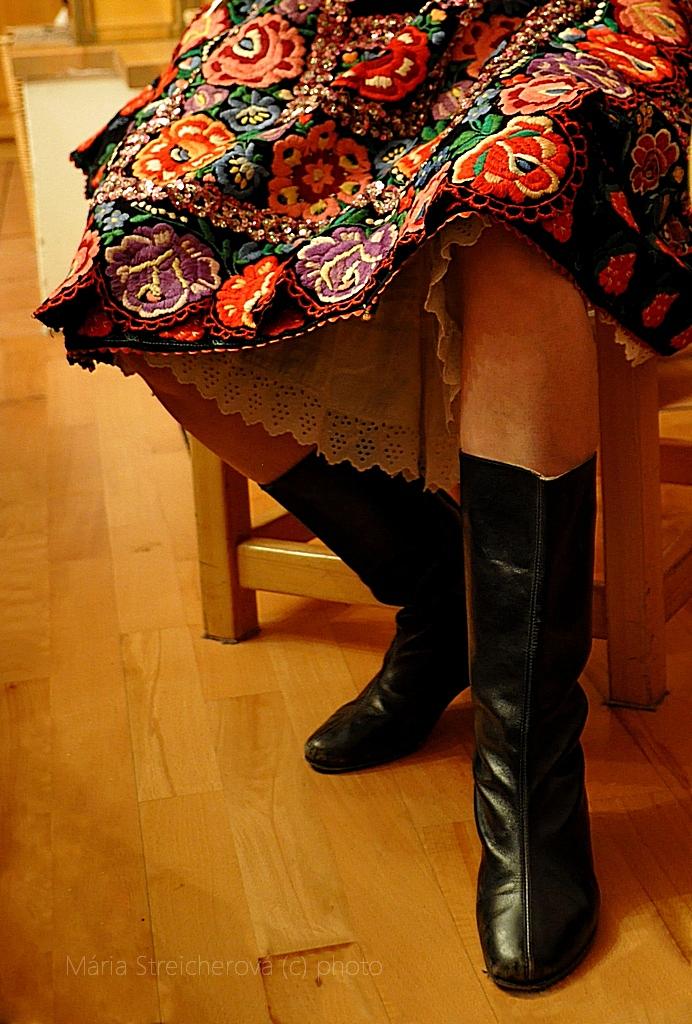 Dievčenské nohy v čiernych čižmičkách a krojovej vyšívanej sukni. Pestrá výšivka kvetinového motívu.