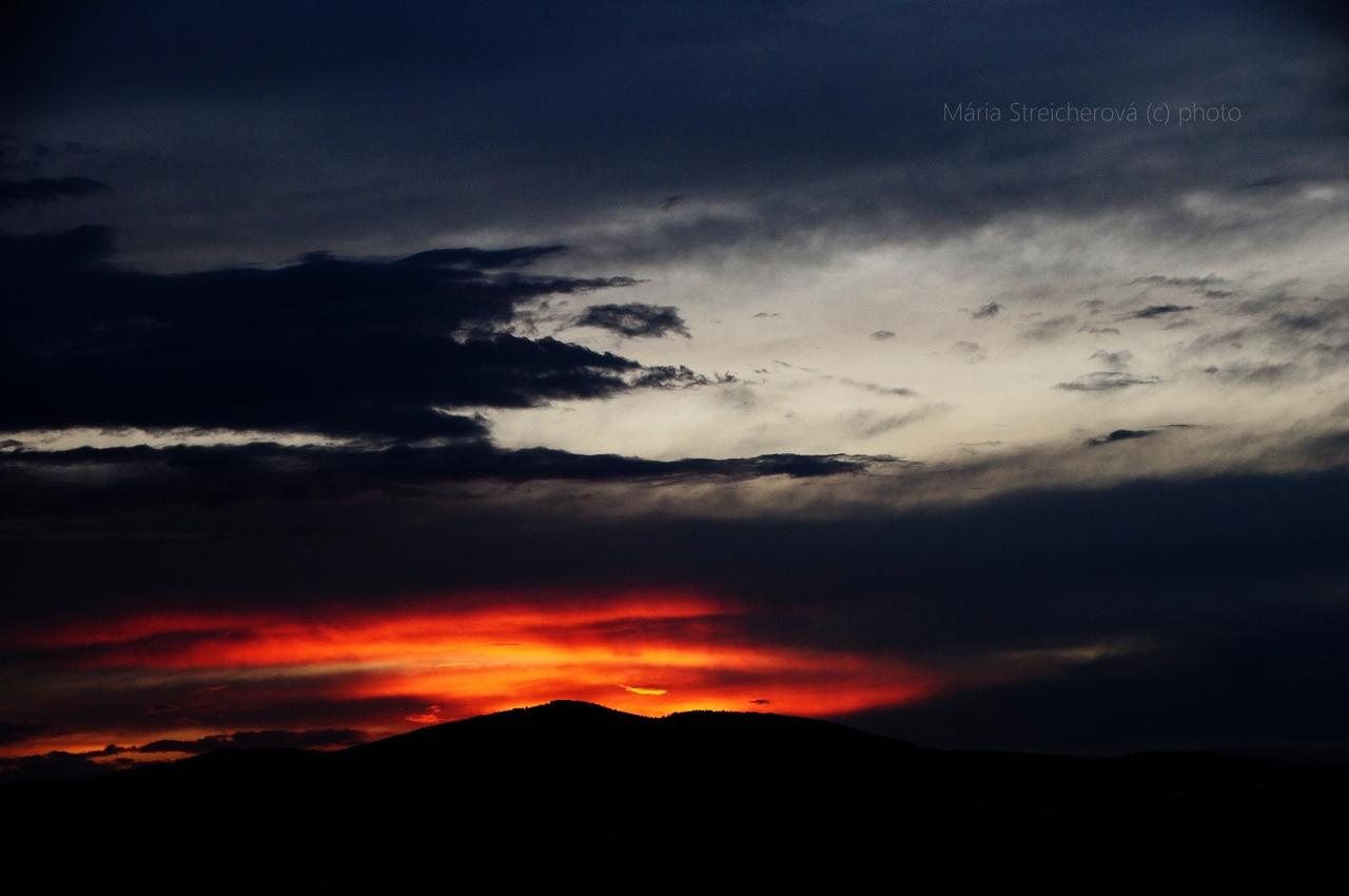 Oranžovočervený odraz slnka na modro sivých oblakoch, zapadajúceho za čierny horizint hôr.
