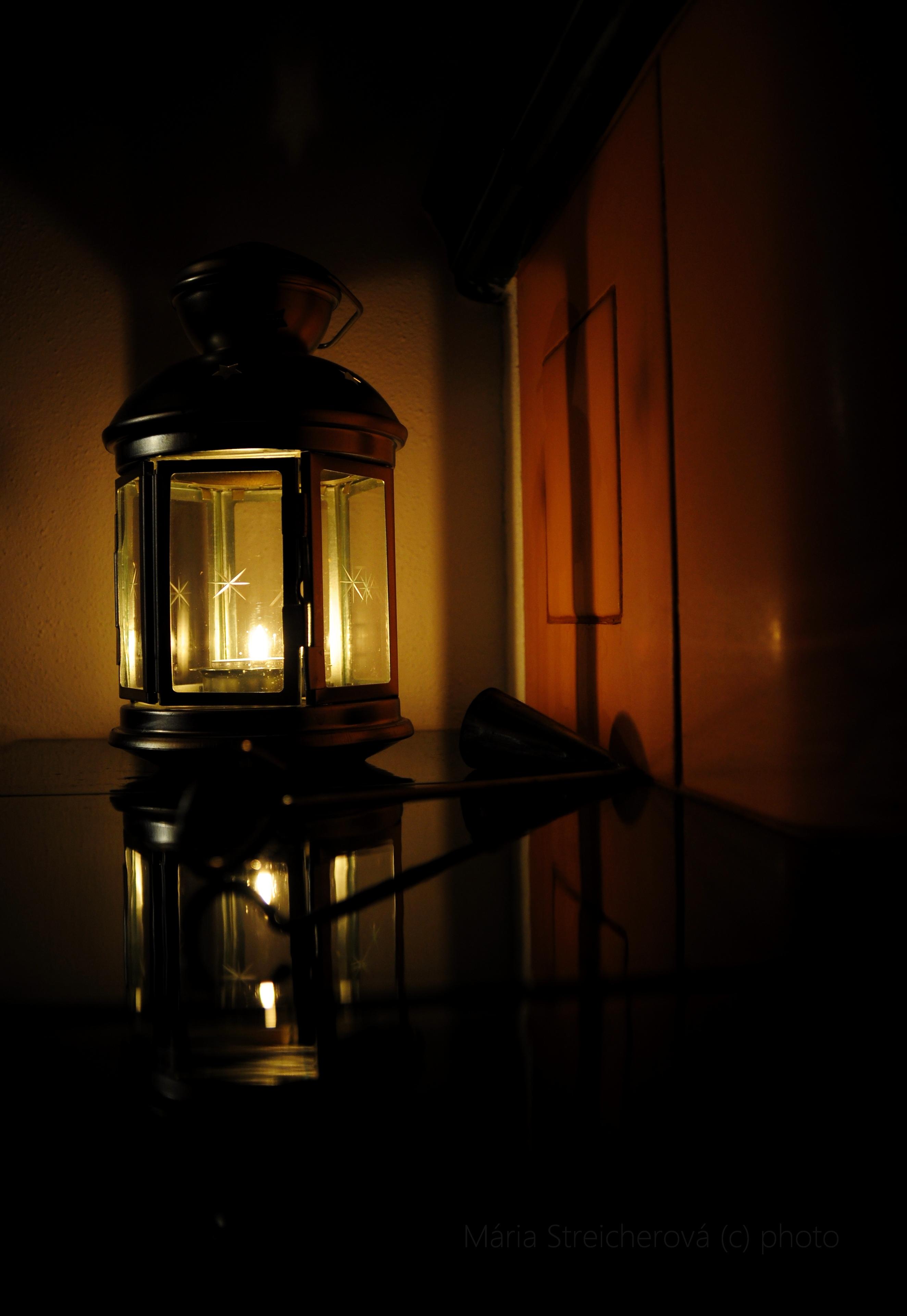Kovový lampáš so sviečkou, zhášadlo a ich odraz na lesklých kachliciach kachľovej pece