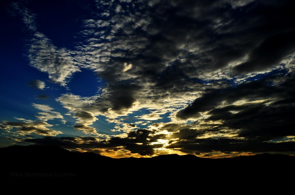 Nebo s čiernymi a bielymi na žlto podsvietenými oblakmi zo svetla zapadajúceho slnka. Čierny horizont, modrá obloha.