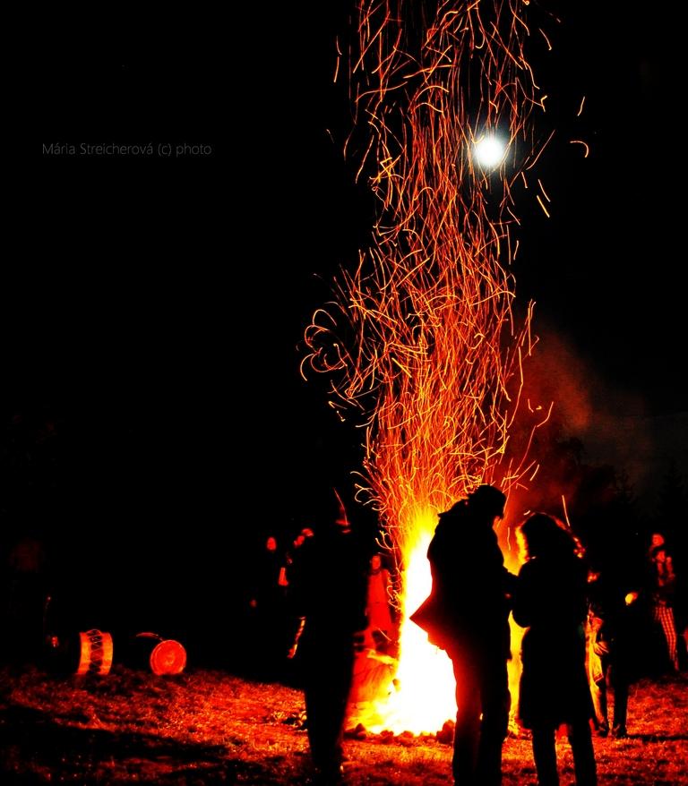 Záber vatry, vyletujúcich iskier a siluet postáv pred ohňom, v pozadí spln mesiaca.
