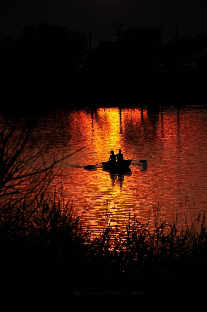 Odraz zapadajúceho slnka na jazernej hladine so siluetou člnu s veslami a s dvomi sediacimi postavami v člne. V popredí siluety pobrežných rastlín, tŕstia a konárov stromov.