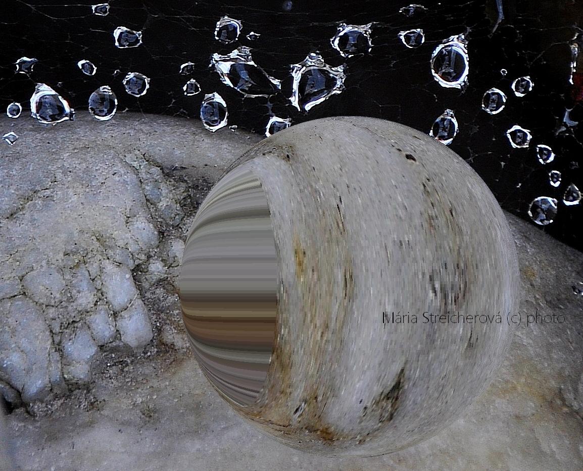Kvapky rosy v pavučine natiahnutej medzi kameňmi s grafickou úpravou vytvárajúcou ilúziu planéty v popredí tohto záberu.