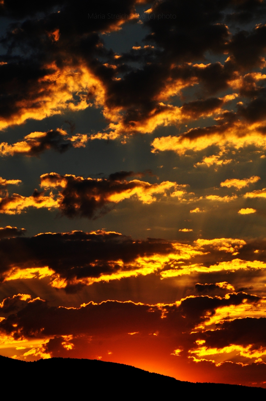 Svetlo zapadajúceho slnka vychádzajúce spoza čierneho horizontu a nasvecujúce žltou žiarou na modrom nebi roztrúsené čierne oblaky.