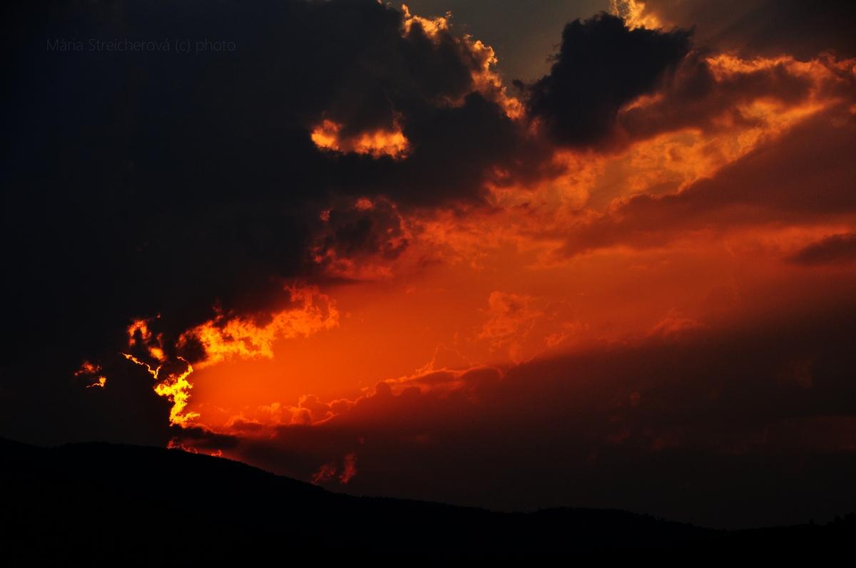 Oranžový západ slnka so slnkom skrytým za zatienenými oblakmi a sčasti aj za horizontom vrchov.