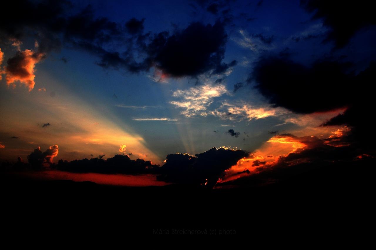 Lúče slnka v oranžovo modrom západe slnka, za čiernymi oblakmi a čiernym horizontom.